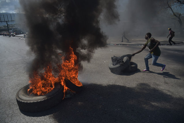 A demonstrator prepares to torch another tire on the fourth day of protests in Port-au-Prince, February 10, 2019, against Haitian President Jovenel Moise and misue of Petrocaribe fund. (Photo by Héctor Retamal/AFP Photo)