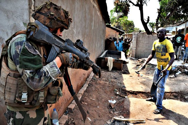 A French soldier of Operation Sangaris asks a man to put down his hammer and shovel during a patrol in Bangui on January 29, 2014. Gunfire erupted on January 29 in Bangui, still plagued by looting despite the security operations of French and African soldiers, now awaiting the reinforcement of a European force whose engagement has been authorized by the United Nations. (Photo by Issouf Sanogo/AFP Photo)