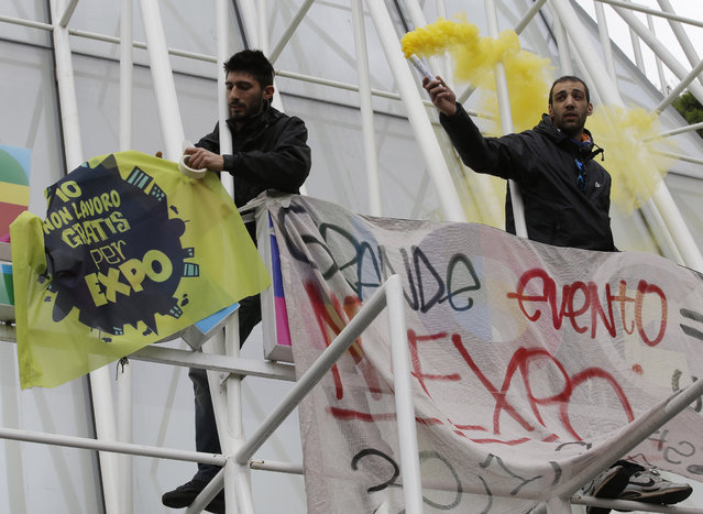 Demonstrators climb the Expo gate during a protest against Expo 2015 in Milan, Italy, Thursday, April 30, 2015. (Photo by Antonio Calanni/AP Photo)