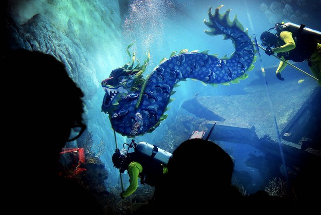 Divers carry a man-made dragon as part of Chinese New Year dragon blessings to wish all their guests boundless energy in the Year of the Horse, at the South East Asia Aquarium at Resorts World Sentosa in Singapore. (Photo by Wong Maye-E/Associated Press)
