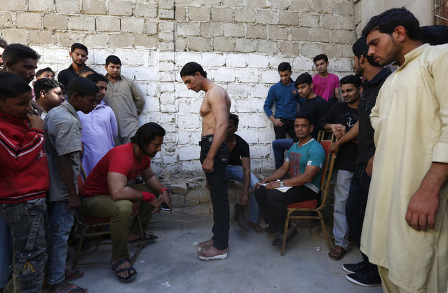 A participant stands on a scale to get signed up for a local bodybuilding and fitness championship in Karachi, Pakistan March 13, 2016. (Photo by Akhtar Soomro/Reuters)