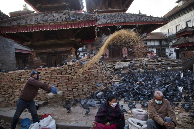 A Nepalese Hindu man feeds pigeons early morning at the Basantapur Durbar Square damaged during the April 25 earthquake in Kathmandu, Nepal, Tuesday, May 5, 2015. Nepal is one of the world's poorest nations, and its economy, largely based on tourism, has been crippled by the earthquake, which left thousands dead. (Photo by Bernat Amangue/AP Photo)