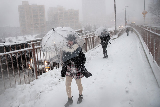 People walk on the pedestrian walkway of the Brooklyn Bridge in the snow, February 9, 2017 in New York City. (Photo by Drew Angerer/Getty Images)