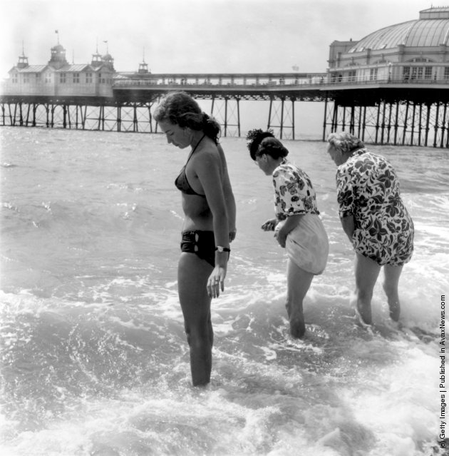 Michele Karsteus (left) paddles with some older holidaymakers at the water's edge, 1951