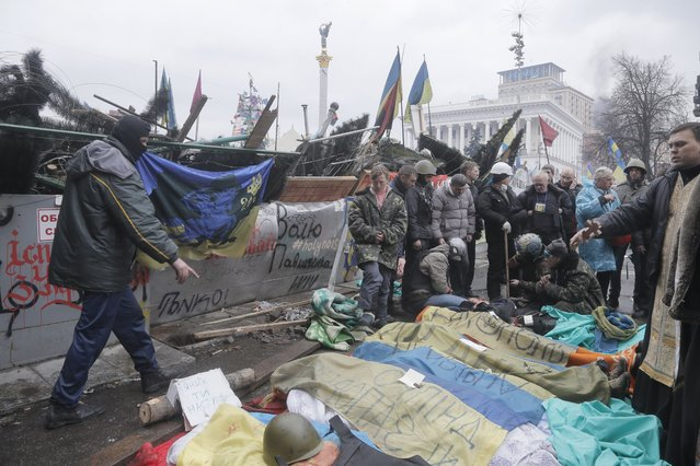 People look at protesters who were killed in clashes with police in Kiev's Independence Square, the epicenter of the country's current unrest, Kiev, Ukraine, Thursday, February 20, 2014. (Photo by Efrem Lukatsky/AP Photo)