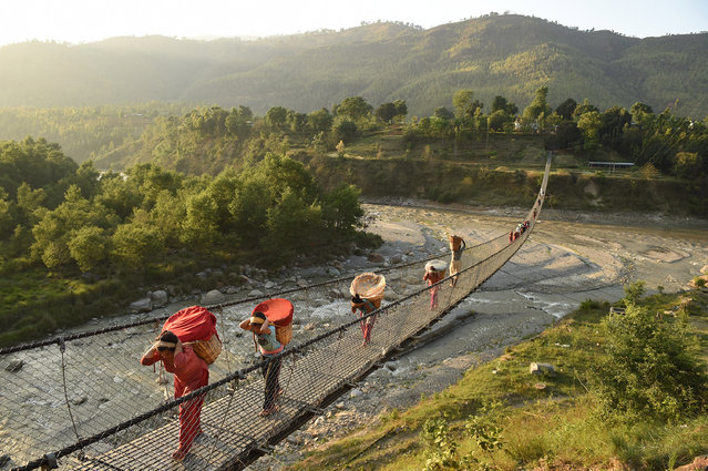 NUWAKOT DISTRICT, NEPAL - MAY 03: People cross a bridge on Sunday May 03, 2015 in the Nuwakot District of Nepal. A deadly earthquake in Nepal has killed thousands. (Photo by Matt McClain/ The Washington Post)