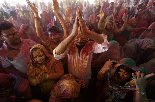 Hindu devotees daubed in colours sing religious songs inside a temple during Holi celebrations in Ahmedabad, India, March 23, 2016. (Photo by Amit Dave/Reuters)