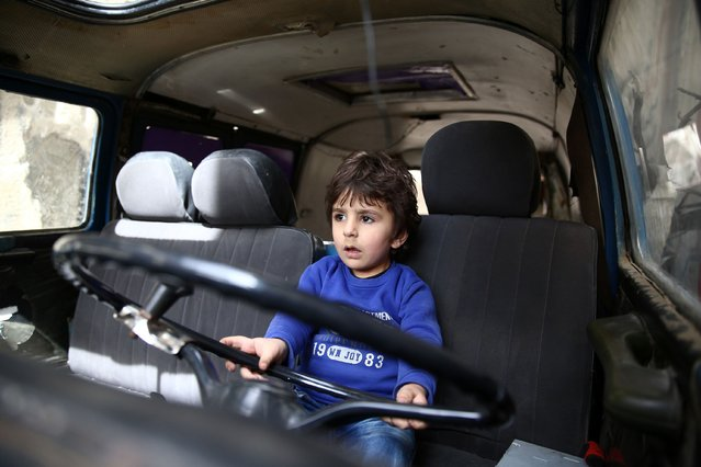 A Syrian boy plays in a vehicle in the al-Qaboun rebel held northeastern suburb of the capital Damascus on March 13, 2016. One in three Syrian children have known nothing but a lifetime of war, UNICEF said, as the country's conflict enters its sixth year this week. Forced from their homes and schools, orphaned by violence and drafted into work or fighting, a generation of Syria's children is being shaped by the conflict, UNICEF said in a new report. (Photo by Abd Doumany/AFP Photo)