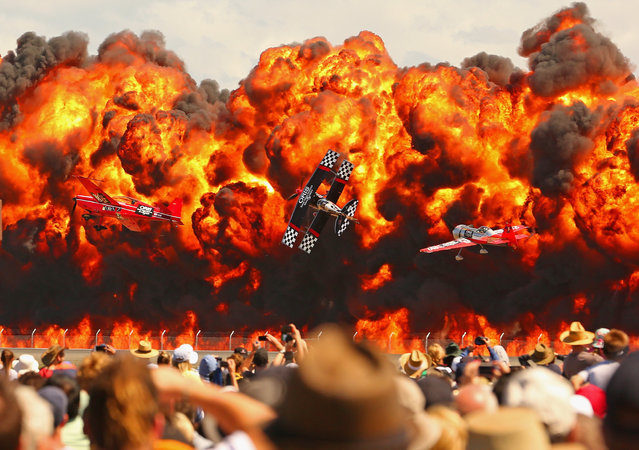 The crowd watches as stunt pilots Melissa Pemberton, Jurgis Kairys and Skip Stewart of The Immortals fly past pyrotechnics as they perform at The Australian International Airshow on March 1, 2015 in Avalon, Australia. (Photo by Scott E. Barbour/Getty Images)