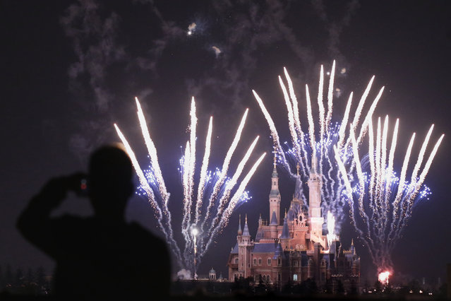 A man uses his mobile to film fireworks near the Enchanted Storybook Castle at the Shanghai Disney Resort in Shanghai, Monday, March 28, 2016. The Disney theme park is scheduled to open on June 16 this year. (Photo by Chinatopix via AP Photo)