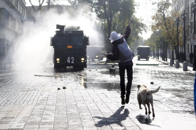A protester throws a bottle at a riot police vehicle as they clash during a demonstration to demand changes in the education system at Santiago, May 14, 2015. (Photo by Ivan Alvarado/Reuters)