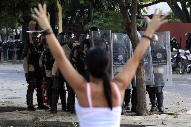 A woman walks past with her arms up in front of police as they clashes with anti-government protesters at Altamira square in Caracas March 3, 2014. Jailed Venezuelan opposition leader Leopoldo Lopez urged sympathizers on Monday to maintain street protests against President Nicolas Maduro as the country's foreign minister prepared to meet the United Nations Secretary General. (Photo by Tomas Bravo/Reuters)