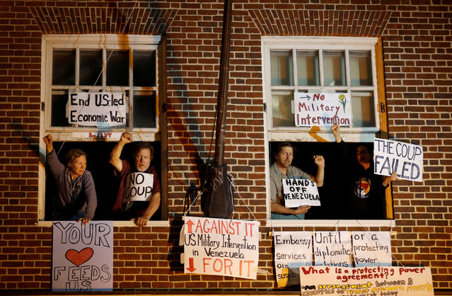 Supporters of Venezuelan President Nicolas Maduro are seen at the window of the Venezuelan embassy after federal agents attempted to evict and arrest four Maduro supporters to end their multi-week occupation, in Washington, U.S., May 13, 2019. (Photo by Carlos Barria/Reuters)