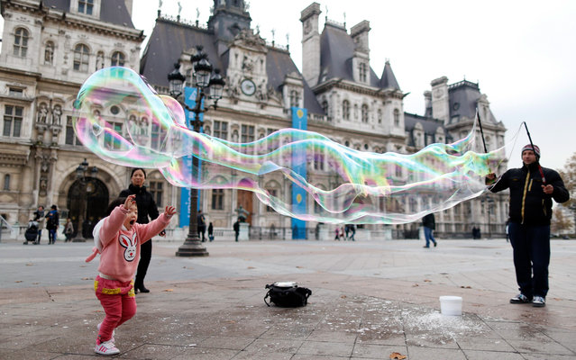 A child tries to reach a giant soap bubble blown from a street artist in front of the Paris Town Hall November 19, 2014. (Photo by Charles Platiau/Reuters)