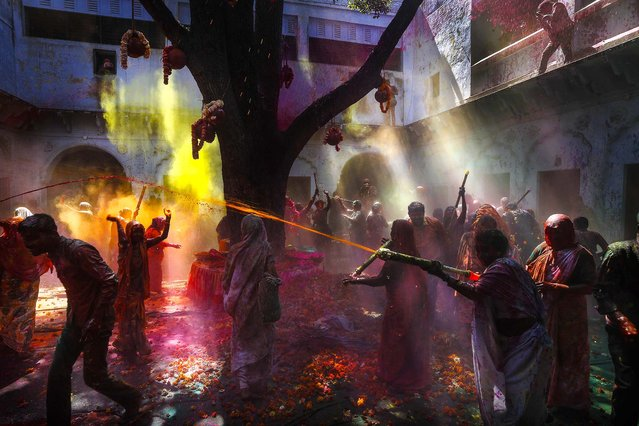 Hindu widows and Harijan, or former untouchable women play with colored water for the first time as part of Holi celebrations at the Meera Sahbhagini Ashram in Vrindavan, India, on March 14, 2014. The widows, many of whom at times have lived desperate lives in the streets of the temple town, celebrated the festival at the century old ashram. After their husband's deaths the women have been banished by their families, for supposedly bringing bad luck, to the town where devotees believe Lord Krishna was born. (Photo by Manish Swarup/Associated Press)