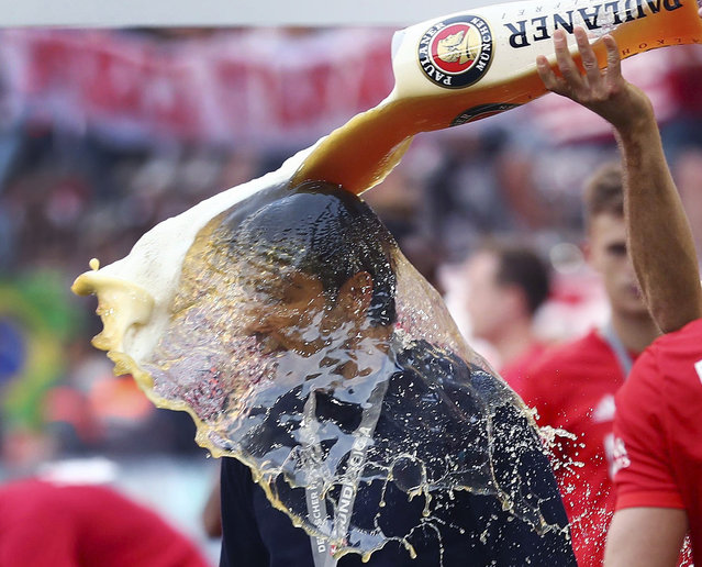 Bayern's Arjen Robben pours beer over coach Niko Kovac to celebrate Bayern's 7th straight Bundesliga title after the German Soccer Bundesliga match between FC Bayern Munich and Eintracht Frankfurt in Munich, Germany, Saturday, May 18, 2019. (Photo by Matthias Schrader/AP Photo)