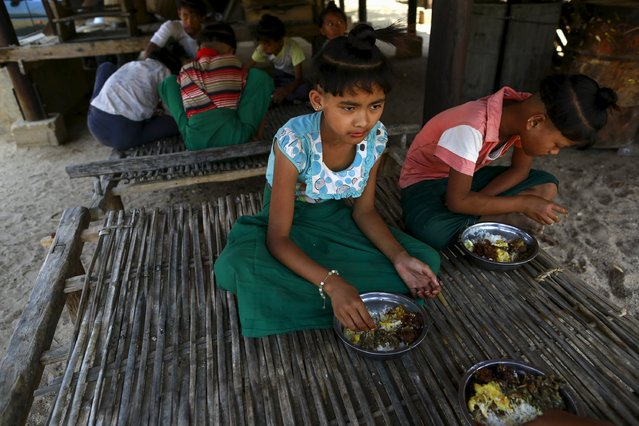Thet Mon Kaw, 9, and her friends who all sport the ancient hairstyle known as Sanyitwine eat their lunch in a monastery at Sat Sat Yo village in Nyaung Oo township, near Myanmar's ancient city Bagan April 17, 2015. (Photo by Soe Zeya Tun/Reuters)