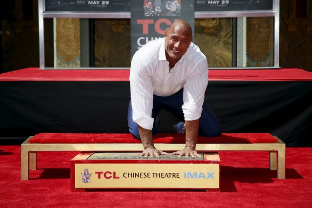 """Actor Dwayne """"The Rock"""" Johnson poses with his hands in cement during his hand and footprints ceremony in the forecourt of the TCL Chinese Theatre in celebration of his new movie """"San Andreas"""", in Hollywood, California May 19, 2015. (Photo by Danny Moloshok/Reuters)"""