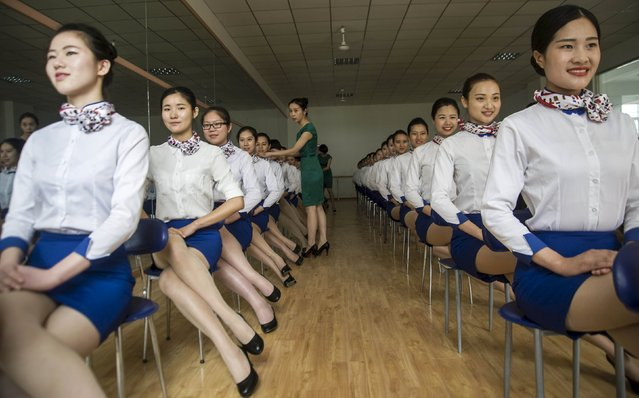 An instructor (C) adjusts the posture of students of flight attendant major during a training session at Anhui Foreign Languages University, in Hefei, Anhui province, China, May 25, 2015. (Photo by Reuters/China Daily)