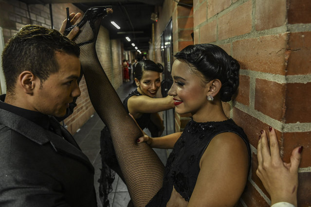 Dancers are warming up backstage during the Tango Dancing Tournament at the XIII International Tango Festival in Medellin, Colombia, on June 18, 2019. The Tango Festival takes place between the 16th and 24th of June. (Photo by Joaquin Sarmiento/AFP Photo)