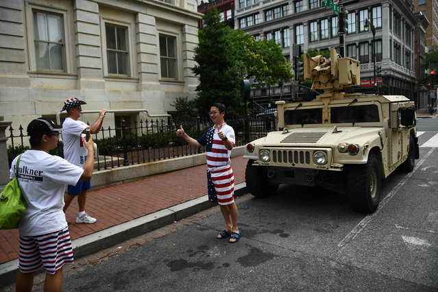 "Independence Day revellers pose in front of a Humvee parked on a street in Washington, DC, on July 4, 2019. Tanks in the heart of Washington, fighter jets screaming overhead, and a speech from the Lincoln Memorial: President Donald Trump has promised the ""show of a lifetime"" Thursday as he turns the Fourth of July into a personal primetime extravaganza. (Photo by Brendan Smialowski/AFP Photo)"