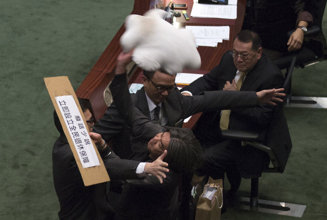 "Pro-democracy lawmaker Leung Kwok-hung throws a cloud-shaped cushion at Hong Kong's Financial Secretary John Tsang to demand a universal retirement protection scheme during the annual budget report at the Legislative Council in Hong Kong February 27, 2013.  The sign reads ""No more nonsense. Set up universal retirement protection scheme now"". (Photo by Tyrone Siu/Reuters)"