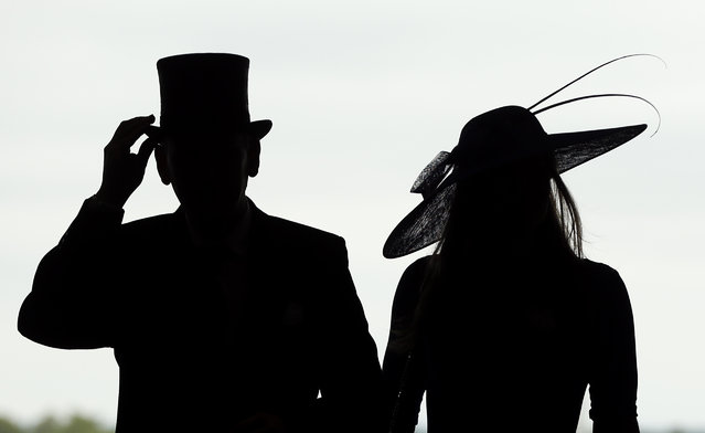 Race goers arrive for the second day of  Royal Ascot horse racing meet at Ascot, England, Wednesday, June 17, 2015. Royal Ascot is the annual five day horse race meeting that Britain's Queen Elizabeth II attends every day of the event.(AP Photo/Alastair Grant)