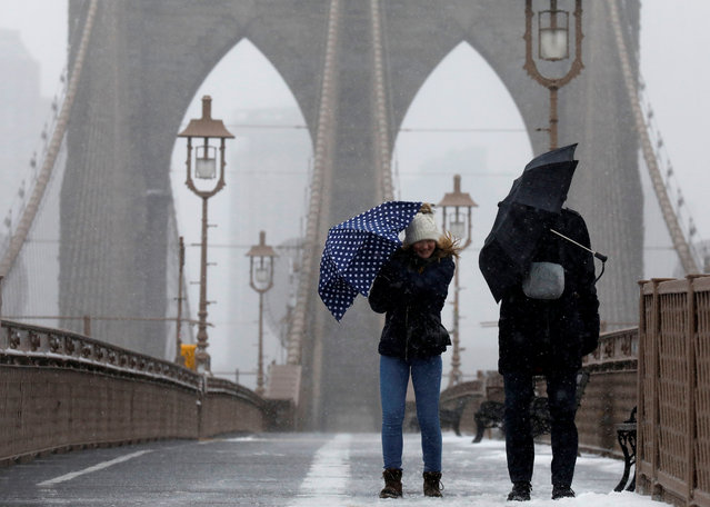 People fight the wind and snow as they walk across the Brooklyn Bridge in New York City, U.S., March 14, 2017. (Photo by Brendan McDermid/Reuters)