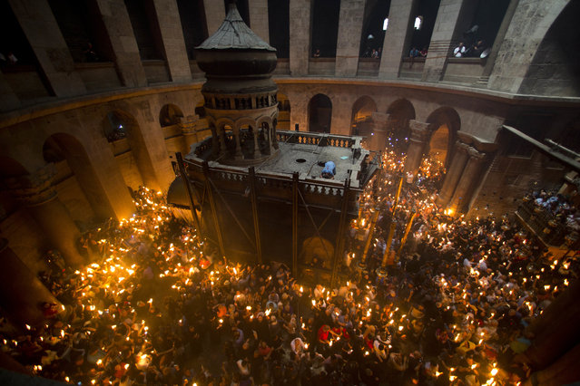 Christian Orthodox pilgrims hold candles during the Holy Fire ceremony in the church of the Holy Sepulchre, traditionally believed to be the burial site of Jesus Christ, Saturday, April 30, 2016 in Jerusalem. Thousands of Christians have gathered in Jerusalem for the ancient fire ceremony that celebrates Jesus' resurrection. (Photo by Dusan Vranic/AP Photo)