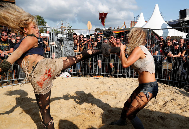 Festivalgoers watch two actors of the Wasteland Warriors movement fight in a cage at the world's largest heavy metal festival, the Wacken Open Air 2019, in Wacken, Germany on August 3, 2019. (Photo by Wolfgang Rattay/Reuters)