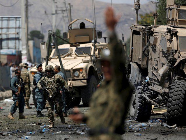 A NATO soldier walks at the site of a suicide bomb attack in Kabul, Afghanistan June 30, 2015. (Photo by Ahmad Masood/Reuters)