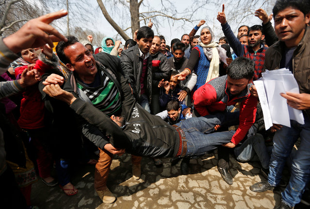 People carry an unconscious teacher after he was injured in clashes with the Indian police during a protest by teachers demanding the regularization of their contractual jobs and hike in salaries, protesters said, in Srinagar, India on March 23, 2017. (Photo by Danish Ismail/Reuters)