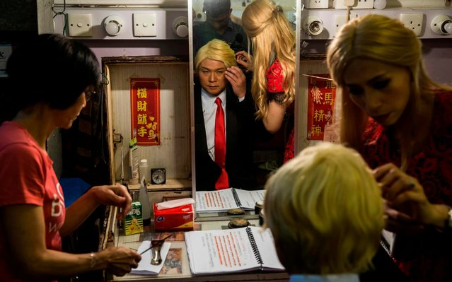 "Actress Man Chan (R), dressed as Ivanka Trump, helps actor Loong Koon-tin (C), changes into US President Donald Trump back stage during a rehearsal of a Cantonese opera called ""Trump on Show"" in Hong Kong on April 11, 2019. In this absurd drama dubbed the ""Trump on Show"", audiences will experience a fantastical mish-mash of current and historic events from the US President Donald Trump's meeting with North Korean leader Kim Jong Un to a fictional meeting with late Chinese leader Mao Zedong. (Photo by Isaac Lawrence/AFP Photo)"