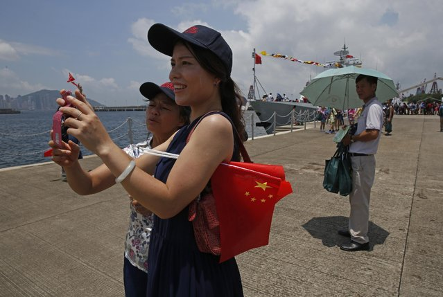 Visitors take pictures near a naval ship at the open day of Stonecutter Island Navy Base of Chinese People's Liberation Army (PLA) n Hong Kong to mark the 18th anniversary of the Hong Kong handover to China in Hong Kong, Wednesday, July 1, 2015. (Photo by Kin Cheung/AP Photo)