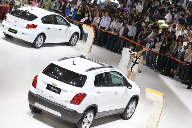 """Visitors gather to watch dancers perform next to GM Chevrolet Trax cars on display during the """"Auto China 2014"""" Beijing International Automotive Exhibition in Beijing on April 21, 2014. (Photo by AFP Photo)"""