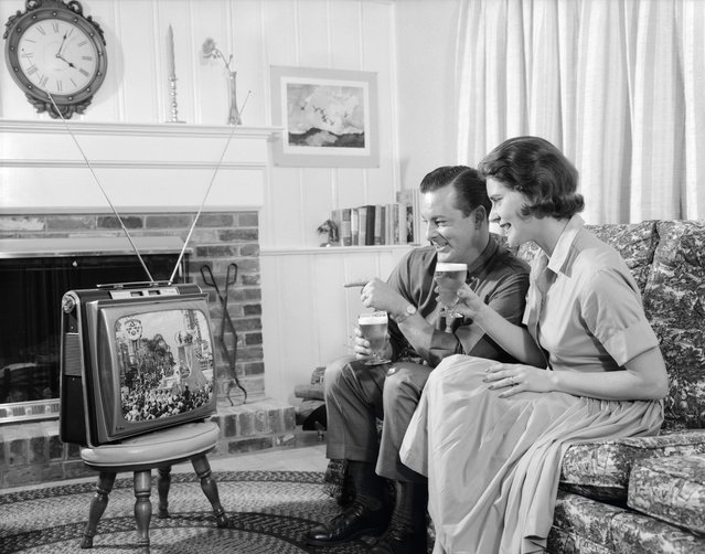 A couple watching a portable TV in the living room. USA, circa 1960s. (Photo by H. Armstrong Roberts/Retrofile/Getty Images)