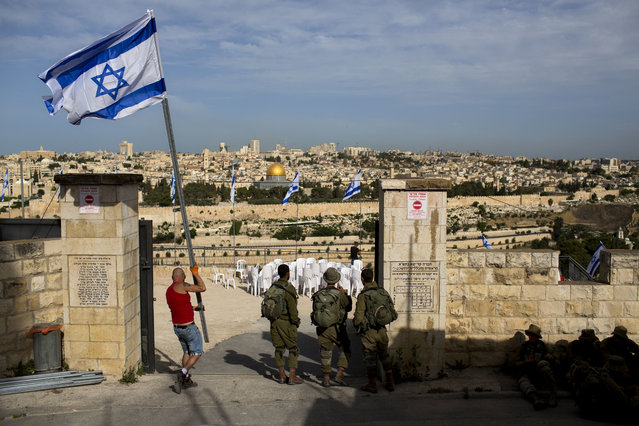 A man carries the Israeli flag during for a ceremony to mark Israel's Memorial Day for fallen soldiers at the Mount of Olives cemetery in east Jerusalem, Tuesday, May 10, 2016. (Photo by Oded Balilty/AP Photo)