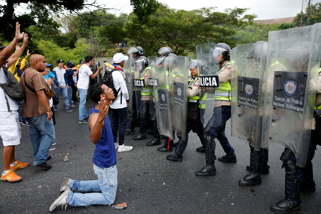 An opposition supporter kneels in front of riot policemen during a rally to demand a referendum to remove President Nicolas Maduro in Caracas, Venezuela, May 11, 2016. (Photo by Carlos Garcia Rawlins/Reuters)
