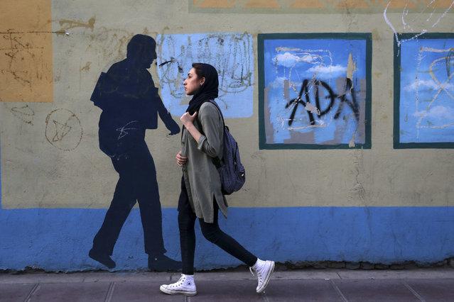 An Iranian woman walks past a mural in a sidewalk in downtown Tehran, Iran, Tuesday, April 26, 2016. (Photo by Vahid Salemi/AP Photo)