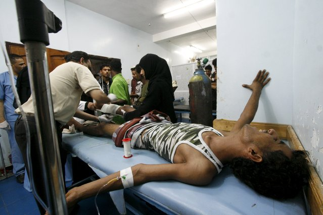 Medics attend to a fighter of the Popular Resistance Committees after he was injured during clashes with Houthi fighters in Yemen's southwestern city of Taiz July 11, 2015. Saudi-led air strikes and heavy shelling between warring factions shook several cities in Yemen on Saturday, residents said, violating a United Nations humanitarian truce which took effect just before midnight. (Photo by Reuters/Stringer)