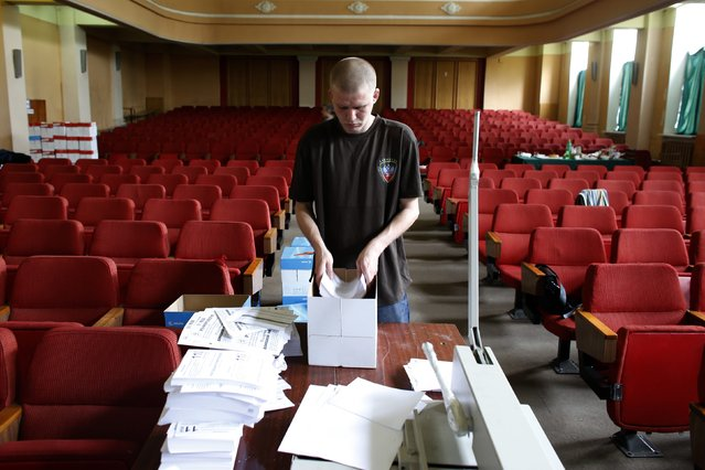 An election worker at the Donetsk self-proclaimed republic's election commission arranges referendum materials inside the commission headquarters in Donetsk, eastern Ukraine May 8, 2014. Pro-Russian separatists in eastern Ukraine ignored a public call by Russian President Vladimir Putin to postpone a referendum on independence, declaring they would go ahead on May 11 with a vote that could lead to war. (Photo by Marko Djurica/Reuters)