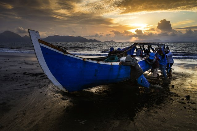 Fishermen push their boat onto the shore upon returning from the sea as the sun sets in Banda Aceh, Indonesia on September 3, 2019. (Photo by Chaideer Mahyuddin/AFP Photo)