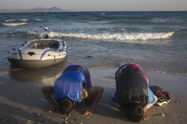 Migrants from Pakistan pray shortly after their arrival on a dinghy from the Turkish coasts to the Greek island of Kos, Wednesday, July 15, 2015. Tens of thousands of migrants have arrived in Greece so far this year, usually on Aegean islands from the nearby Turkish coast, overwhelming local authorities. Aid groups say Greece urgently needs more help from the European Union to deal with the influx. (Photo by Santi Palacios/AP Photo)