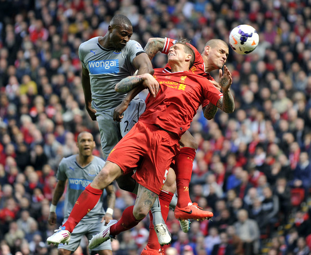 Liverpool's Daniel Agger, center, and Martin Skrtel, right, jump for the ball with Newcastle United's Shola Ameobi during their English Premier League soccer match at Anfield in Liverpool, England, Sunday May 11, 2014. (Photo by Clint Hughes/AP Photo)