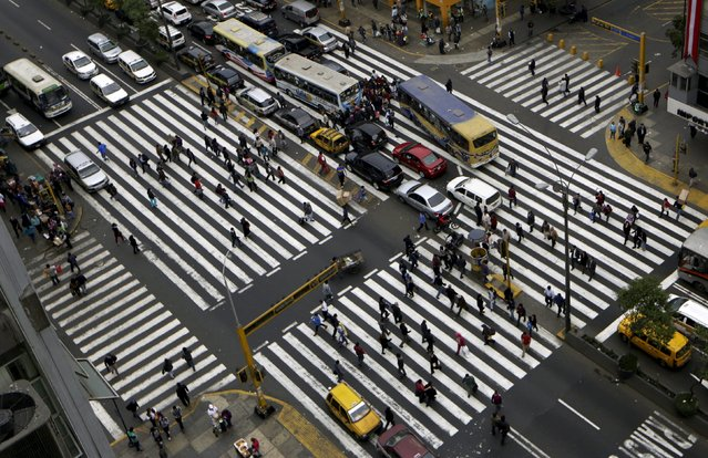 Pedestrians walk on crosswalk at Abancay Avenue in downtown Lima, July 17, 2015. (Photo by Mariana Bazo/Reuters)