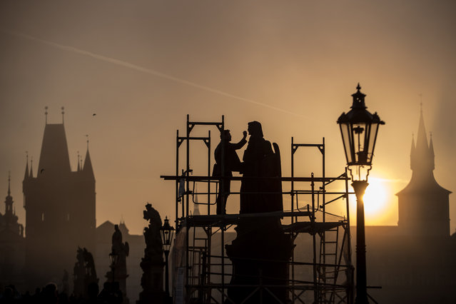 A restorer works on statue on Charles Bridge early in the foggy morning in Prague, Czech Republic, 25 October 2019. Meteorologists predict sunny weather with temperatures around 18 degrees Celsius in the next days in Czech Republic. (Photo by Martin Divisek/EPA/EFE)