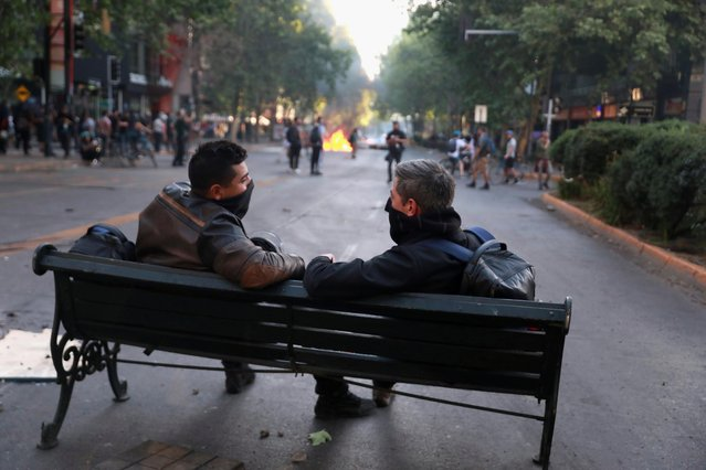 People sit on a bench in the middle of a road as demonstrators protest against Chile's government in Santiago, Chile on November 6, 2019. (Photo by Henry Romero/Reuters)
