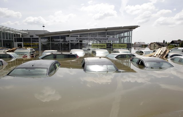 Cars at a car dealership are seen in the flooded village of Fischerdorf, near Deggendorf June 7, 2013. REUTERS/Michaela Rehle