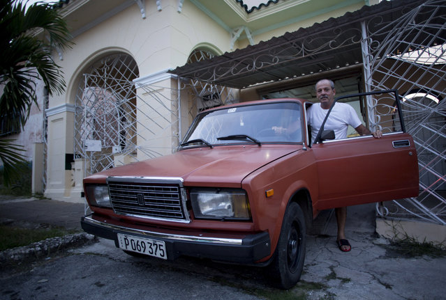 Leandro Cueto poses for a portrait with his car, a Russian 1986 Lada, at his home in Havana, Cuba, Tuesday, October 6, 2019. Cueto said he bought the car new in 1986, which requires repairs every five years, and has repainted it once. (Photo by Ismael Francisco/AP Photo)