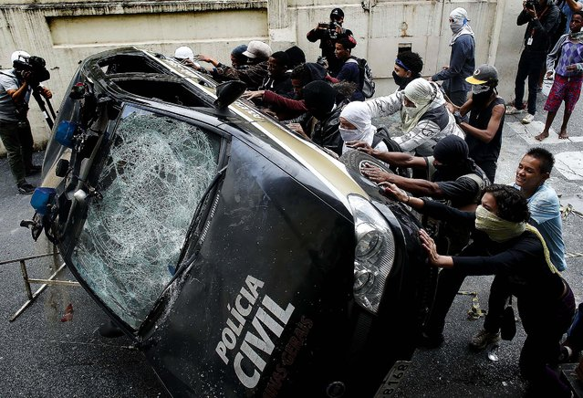 Demonstrators push over a police car during a protest demanding better public services and against the money spent on the World Cup tournament, in Belo Horizonte, Brazil, on June 12, 2014. (Photo by Victor R. Caivano/Associated Press)